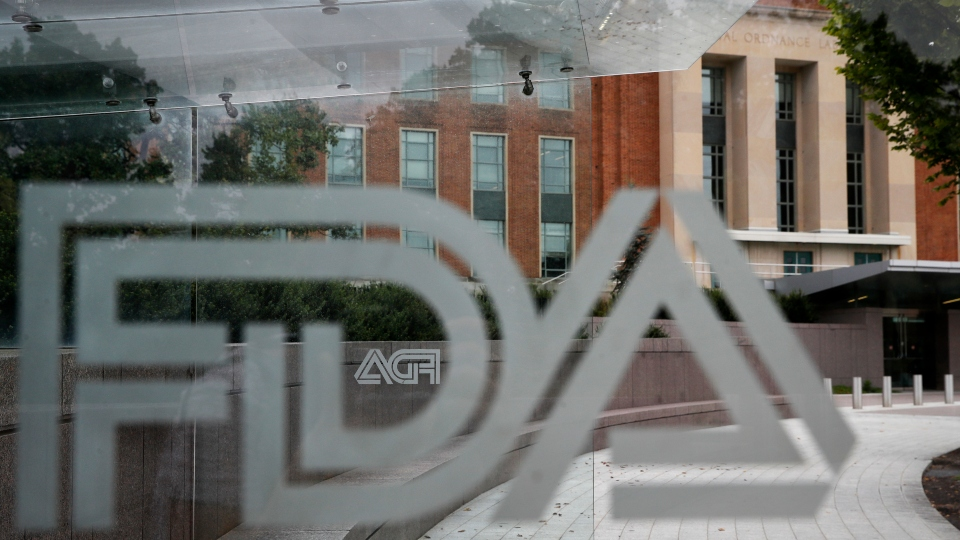 FILE - This Thursday, Aug. 2, 2018, file photo shows the U.S. Food and Drug Administration building behind FDA logos at a bus stop on the agency's campus in Silver Spring, Md. On Friday, Sept. 24, 2021, The Associated Press reported on stories circulating online incorrectly asserting that experts with the Food and Drug Administration revealed that the COVID-19 vaccines are killing at least two people for every person they save. But FDA experts did not say this, and strongly refuted this false claim in an email to The Associated Press. A speaker who is not affiliated with the FDA made these statements during the open public hearing portion of a Sept. 17 FDA vaccine advisory panel meeting.