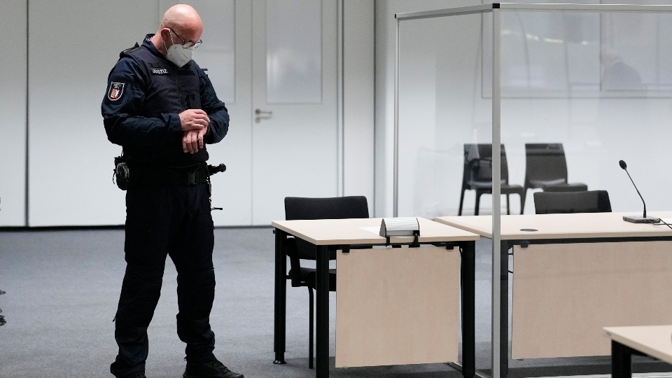 A judicial officer looks at his watch prior to a trail against a 96-year-old former secretary for the SS commander of the Stutthof concentration camp at the court room in Itzehoe, Germany, Thursday, Sept. 30, 2021. The woman who is charged of more than 11,000 counts of accessory to murder has not appeared and is wanted by warrant. (AP Photo/Markus Schreiber, Pool)