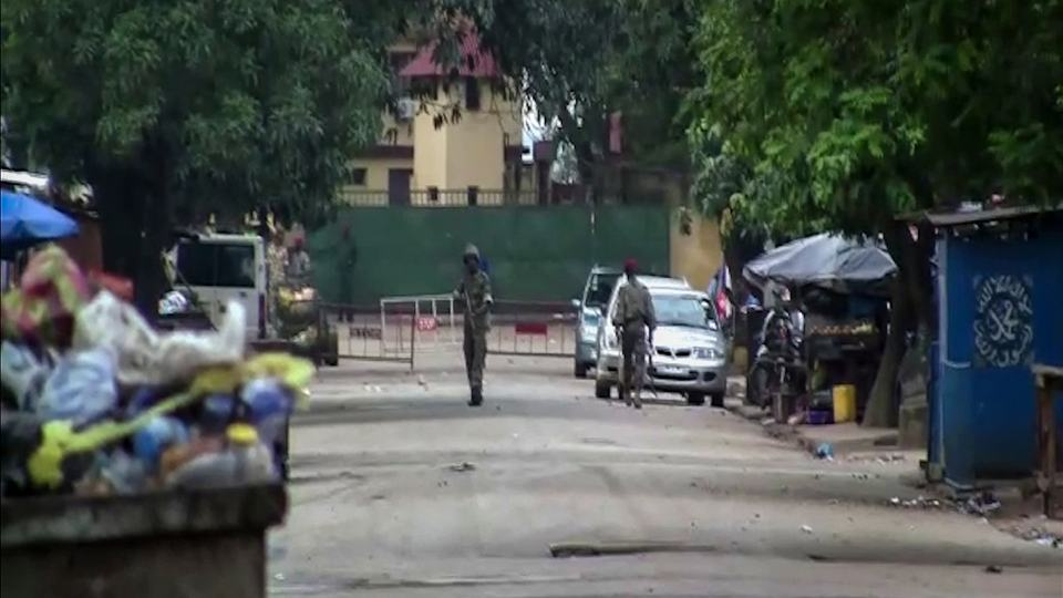 In this image made from video, unidentified soldiers are seen near the presidential palace in the capital Conakry, Guinea Sunday, Sept. 5, 2021. Mutinous soldiers detained President Alpha Conde on Sunday after hours of heavy gunfire rang out near the presidential palace, then announced on state television that the government had been dissolved in an apparent coup d'etat. (AP Photo)