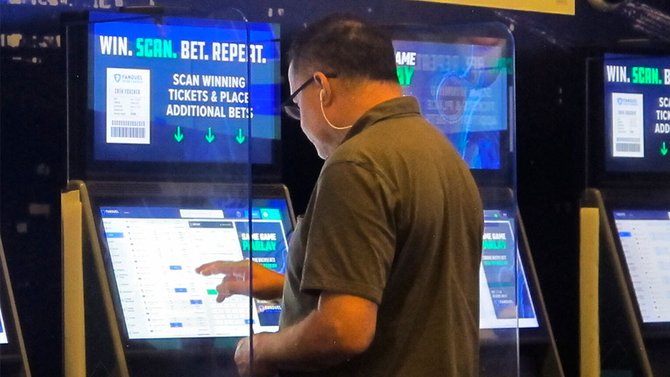 A gambler places a bet at the FanDuel sportsbook in East Rutherford N.J. on Aug. 30, 2021. The American Gaming Association says 45.2 million Americans plan to bet on NFL games this season, up 36% from last year