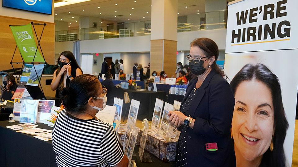 Marriott human resources recruiter Mariela Cuevas, left, talks to Lisbet Oliveros, during a job fair at Hard Rock Stadium, Friday, Sept. 3, 2021, in Miami Gardens, Fla.
