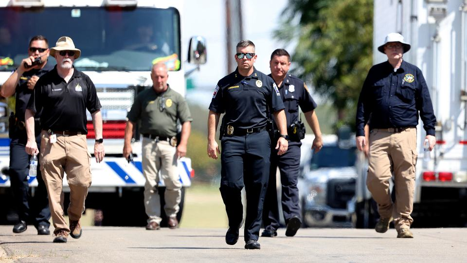 Lake Worth Police Chief J.T. Manoushagian, center, walks down Foster Drive near the location where a military training jet crashed on Sunday, Sept. 19, 2021, in Lake Worth, Texas. The jet crashed Sunday in a neighborhood near Fort Worth, Texas, injuring the two pilots and damaging three homes but not seriously hurting anyone on the ground, authorities said. (Amanda McCoy/Star-Telegram via AP)