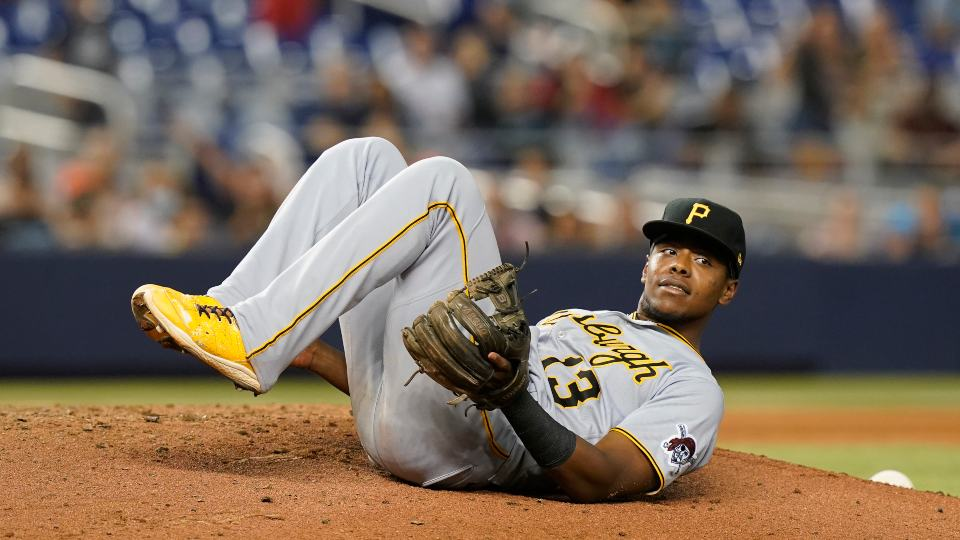 Pittsburgh Pirates third baseman Ke'Bryan Hayes (13) lies on the pitcher's mound after he fell while trying to catch a pop fly by Miami Marlins' Lewis Brinson, who ended up with a single during the ninth inning of a baseball game Saturday, Sept. 18, 2021, in Miami. The Pirates won 6-3. (AP Photo/Marta Lavandier)