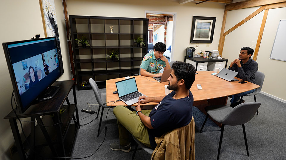 RunX CEO Ankur Dahiya, center, takes part in a video meeting with employees JD Palomino, top left, and Nitin Aggarwal, right, at a rented office in San Francisco, Friday, Aug. 27, 2021