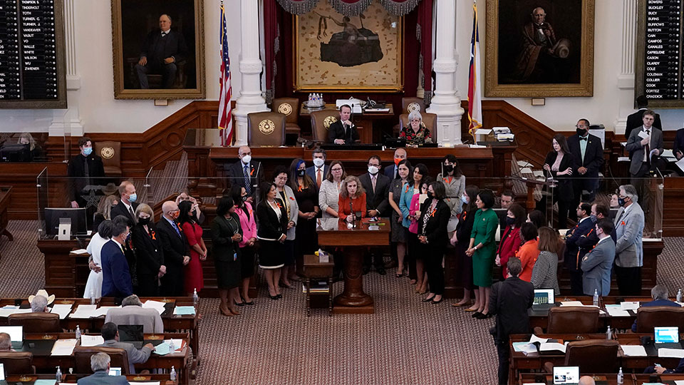 Texas state Rep. Donna Howard, D-Austin, center at lectern, stands with fellow lawmakers in the House Chamber in Austin, Texas