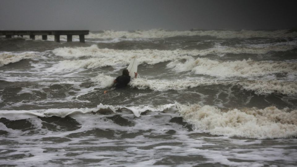 A surfer tries to paddle through the surf as wind and rain from Tropical Storm Nicholas batters the area Monday, Sept. 13, 2021, along the seawall in Galveston, Texas. (Jon Shapley/Houston Chronicle via AP)A surfer tries to paddle through the surf as wind and rain from Tropical Storm Nicholas batters the area Monday, Sept. 13, 2021, along the seawall in Galveston, Texas. (Jon Shapley/Houston Chronicle via AP)