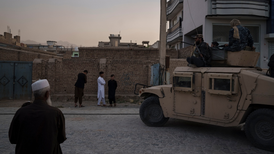 Afghans watch as Taliban fighters ride atop a humvee after detaining four men who got involved in a street fight in Kabul, Afghanistan, Tuesday, Sept. 21, 2021. The Taliban are promising a return of some of their harsh punishments that made them notorious. That has many Afghans afraid, but some also say they are giving the Taliban a chance if it means greater stability and fewer corrupt officials reaching into their pockets. (AP Photo/Felipe Dana)