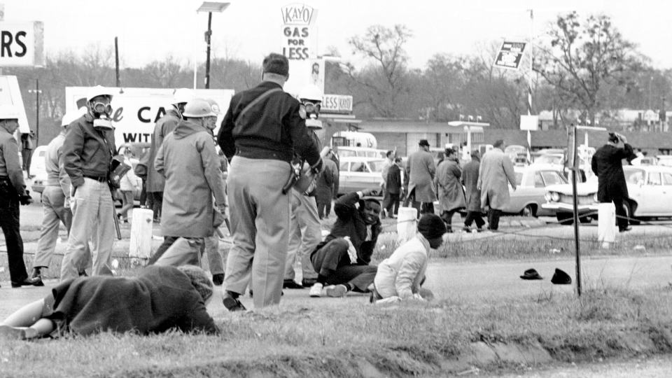"""FILE - In this March 7, 1965, file photo, civil rights demonstrators struggle on the ground as state troopers break up a march in Selma, Ala. The world knows the names of John Lewis and a few more of the voting rights demonstrators who walked across Selma's Edmund Pettus Bridge in 1965 only to be attacked by Alabama state troopers on a day that came to be called """"Bloody Sunday."""" A new project aims to identify more of the hundreds of people who were involved in the protest. (AP Photo/File)"""