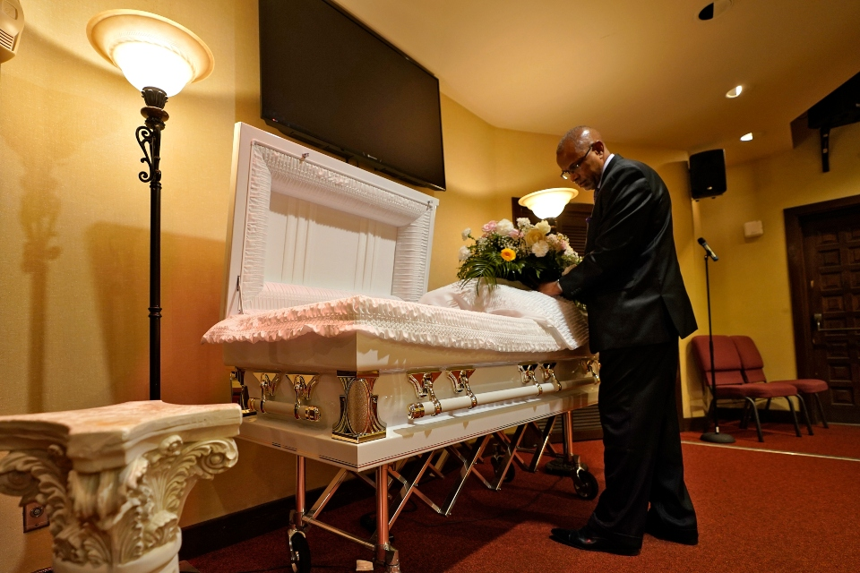 FILE - In this Thursday, Sept. 2, 2021 file photo, a funeral director arranges flowers on a casket before a service in Tampa, Fla. According to a study published Thursday, Oct. 7, 2021, by the medical journal Pediatrics, the number of U.S. children orphaned during the COVID-19 pandemic may be larger than previously estimated, and the toll has been far greater among Black and Hispanic Americans