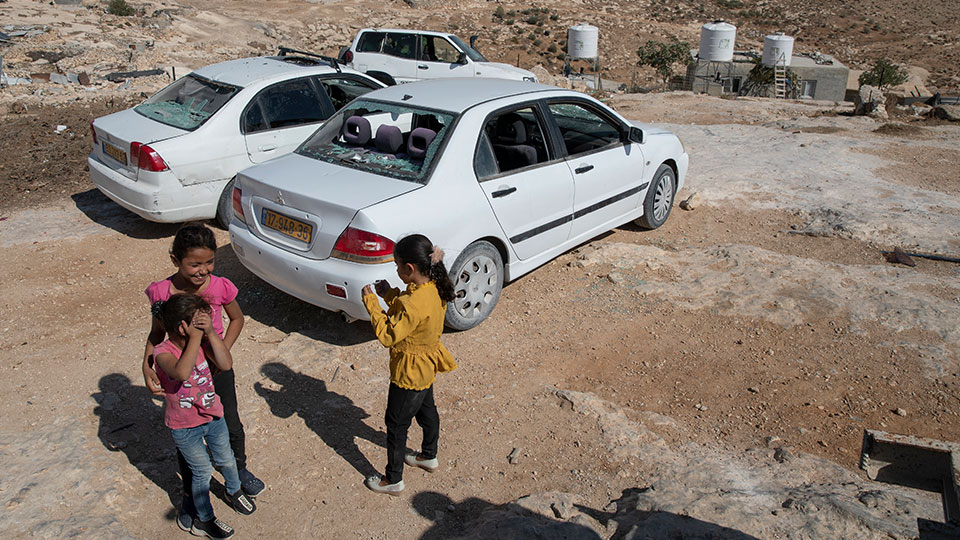 Girls play around smashed vehicles following a settlers' attack from nearby settlement outposts on the Palestinian Bedouin community, in the West Bank village of al-Mufagara, near Hebron, Thursday, Sept. 30, 2021