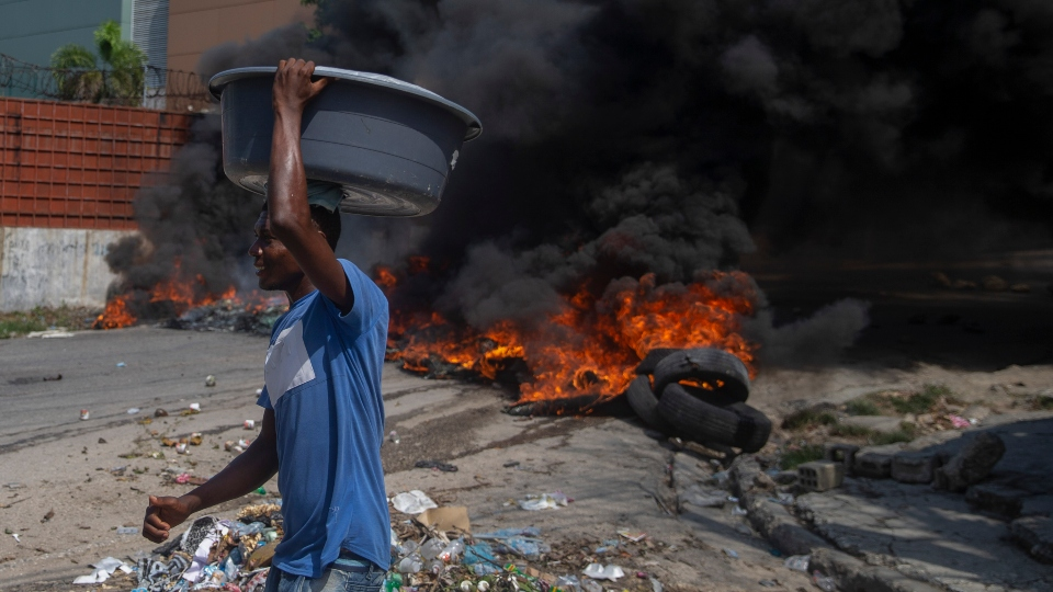 Burning tires block a road, set by protesters in Port-au-Prince, Haiti, Monday, Oct. 18, 2021. Workers angry about the nation's lack of security went on strike in protest two days after 17 members of a U.S.-based missionary group were abducted by a violent gang. (AP Photo/Joseph Odelyn)