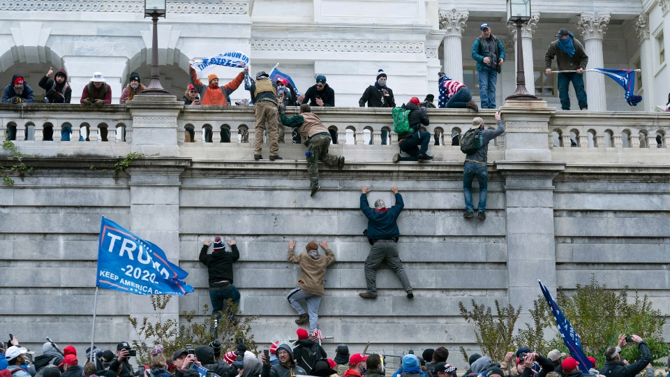 FILE - In this Jan. 6, 2021 file photo, violent insurrectionists loyal to President Donald Trump scale the west wall of the the U.S. Capitol in Washington. In the nearly nine months since Jan. 6, federal agents have managed to track down and arrest more than 600 people across the U.S. believed to have joined in the riot at the Capitol. Getting those cases swiftly to trial is turning out to be an even more difficult task.