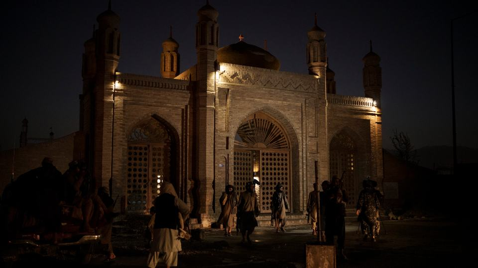 """Taliban fighters walk at the entrance of the Eidgah Mosque after an explosion in Kabul, Afghanistan, Sunday, Oct. 3, 2021. A bomb exploded in the entrance of the mosque in the Afghan capital on Sunday leaving a """"number of civilians dead,"""" a Taliban spokesman said. (AP Photo/Felipe Dana)"""