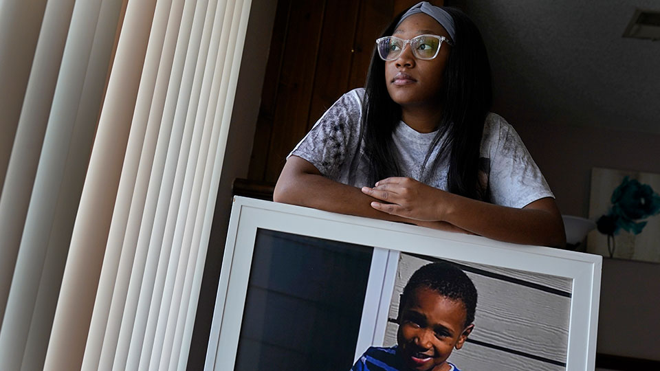 Charron Powell stands with a photo of her son, LeGend Talieferro, at her home in Raytown, Mo. on Sunday, Oct. 3, 2021