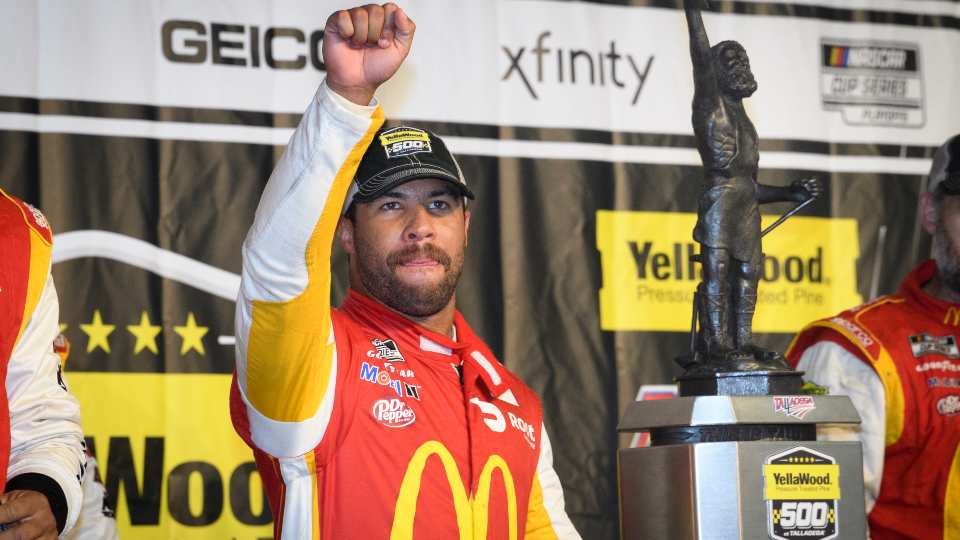 Bubba Wallace celebrates next to the trophy after winning a NASCAR Cup series auto race Monday, Oct. 4, 2021, in Talladega, Ala. The race was stopped mid race due to rain.