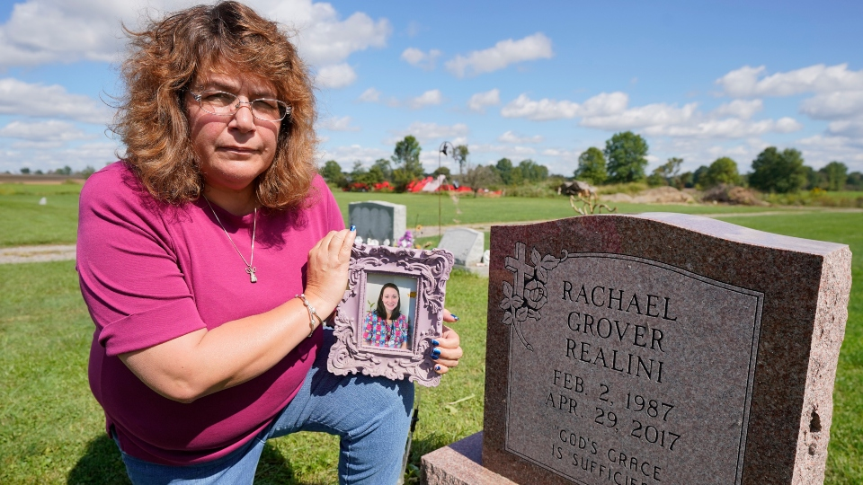 Sharon Grover holds a photograph of her daughter, Rachael, over the gravesite at Fairview Cemetery, Tuesday, Sept. 28, 2021, in Mesopotamia, Ohio. Grover believes her daughter started using prescription painkillers around 2013 but missed any signs of her addiction as her daughter, the oldest of five children, remained distanced.