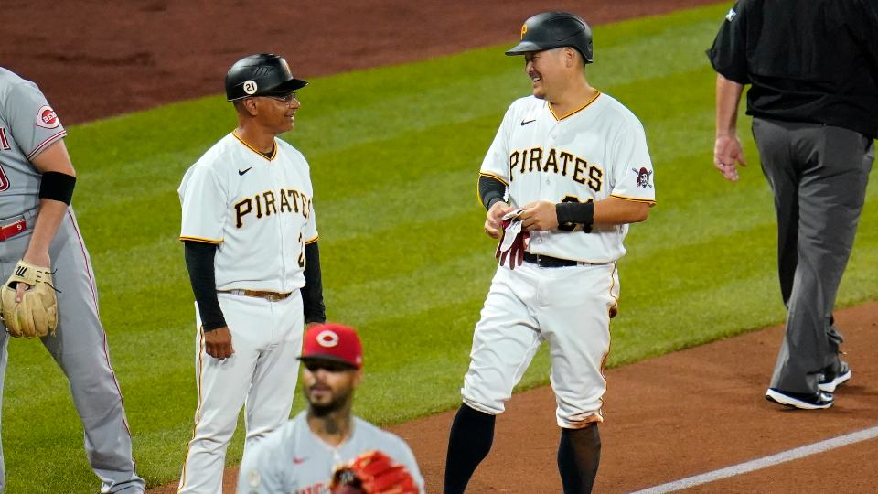 Pittsburgh Pirates' Yoshi Tsutsugo, right, stands on third, talking with coach Joey Cora, left, after hitting an RBI double and advancing on an error during the third inning of the team's baseball game against the Cincinnati Reds on Wednesday, Sept. 15, 2021, in Pittsburgh. (AP Photo/Gene J. Puskar)