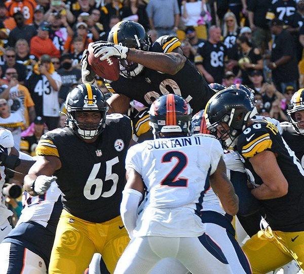 Pittsburgh Steelers running back Najee Harris, top, leaps over the goal line for a touchdown during the first half of an NFL football game against the Denver Broncos in Pittsburgh, Sunday, Oct. 10, 2021
