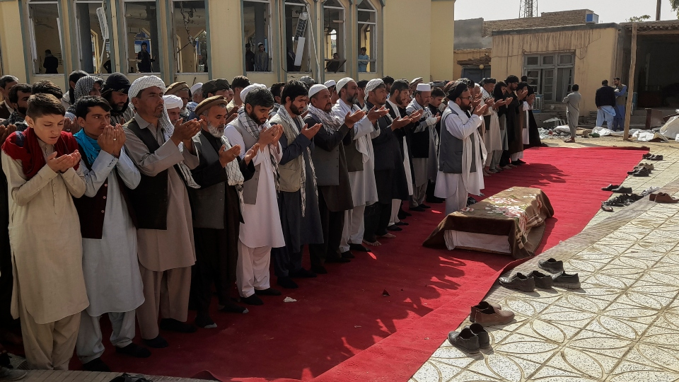 Relatives and residents pray during a funeral ceremony for victims of a suicide attack at the Gozar-e-Sayed Abad Mosque in Kunduz, northern Afghanistan, Saturday, Oct. 9, 2021. The mosque was packed with Shiite Muslim worshippers when an Islamic State suicide bomber attacked during Friday prayers, killing dozens in the latest security challenge to the Taliban as they transition from insurgency to governance.
