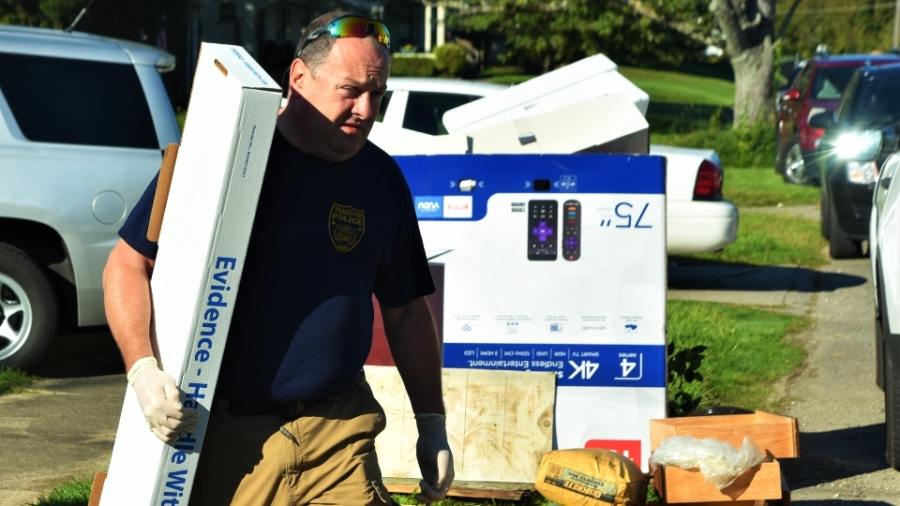 """Youngstown police Detective Sgt. Michael Lambert Friday carries evidence out of a home in the 500 block of Cambridge Avenue police searched as part of an """"ongoing series of investigations"""""""